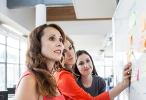 Three businesswomen presenting ideas on office whiteboard